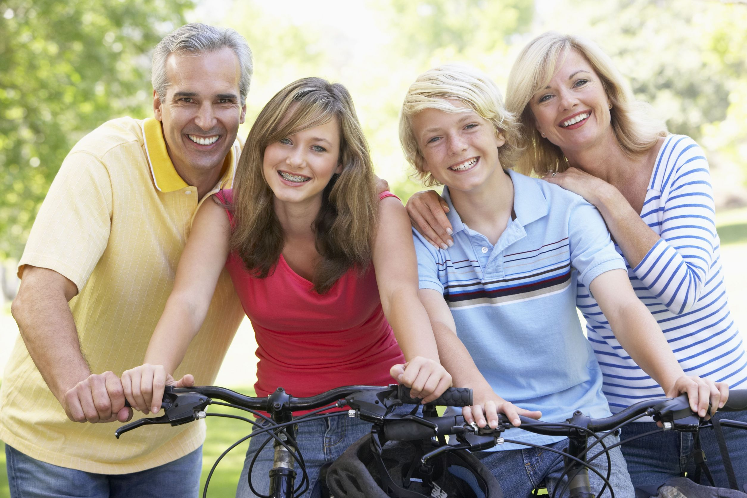 Family smiling while riding bicycles